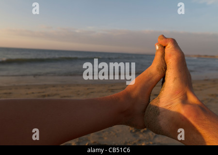 Man and girl feet together on beach - Stock Photo