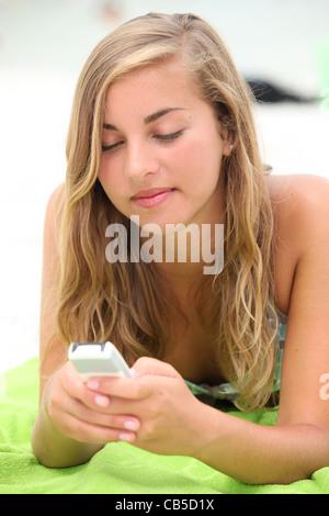 Teenage girl texting on the beach - Stockfoto