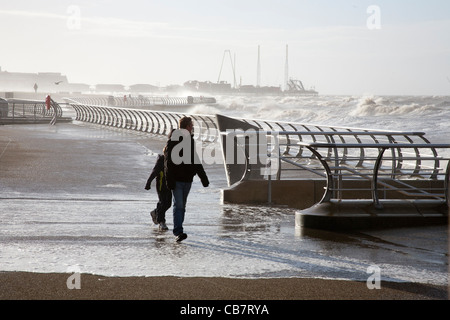 Man and child walking on the Promenade during the High tide at Blackpool, Lancashire, UK - Stock Photo