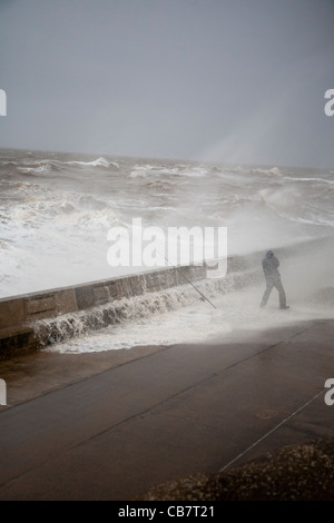 Fisherman engulfed with Spray at the High tide at Blackpool - Stock Photo