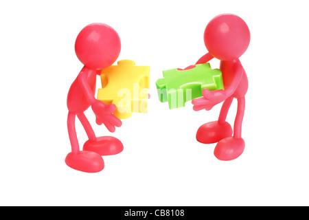 Faceless figurines matching jigsaw puzzle blocks on white background - Stock Photo
