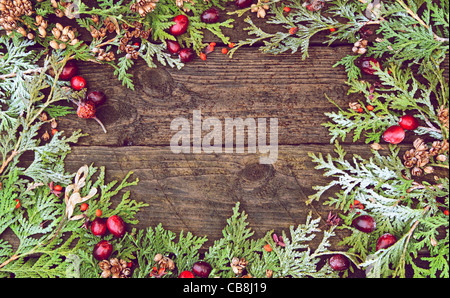 Richly toned Christmas background with cedar sprigs, berries, and maple keys on a grunge wood backdrop with copy - Stock Photo