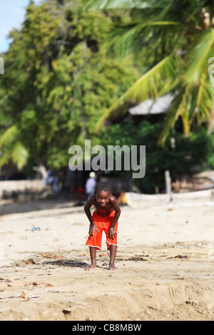 A young boy with in hands on his knees, in orange shorts or trunks, smiling at the beach, Ampangorinana, Nosy Komba, - Stock Photo