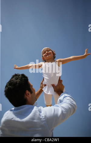 Man lifting his daughter in the air - Stockfoto