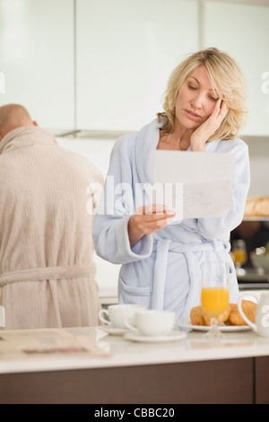 Stressed woman reading mail in bathrobe - Stock Photo