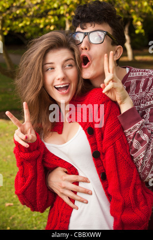 Teenage couple making faces in park - Stockfoto
