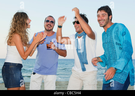 Friends laughing together on beach - Stock Photo