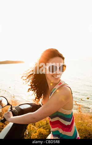 Smiling women riding scooter - Stockfoto