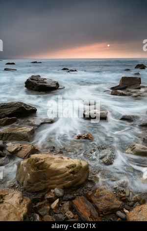 Time lapse view of waves on rocky beach - Stock Photo
