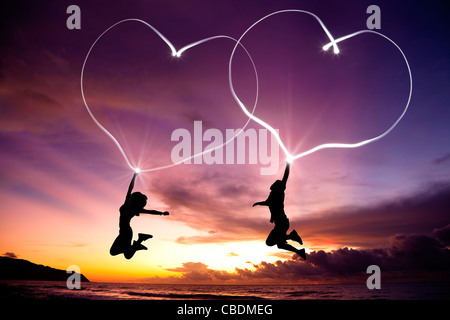 young couple jumping and drawing connected hearts by flashlight in the air on the beach before sunrise - Stock Photo