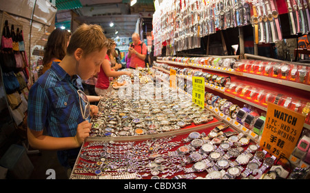 Young tourists looking at watches in the famous Temple Street night market, Kowloon, Hong Kong, China - Stock Photo