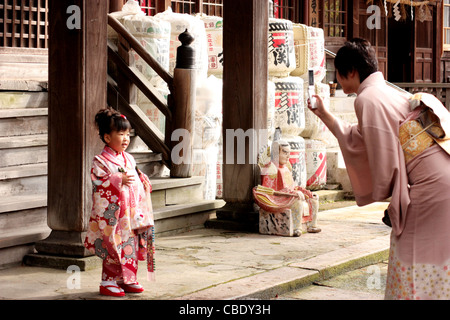 A Japanese mother photographing her daughter dressed in a traditional dress. - Stock Photo