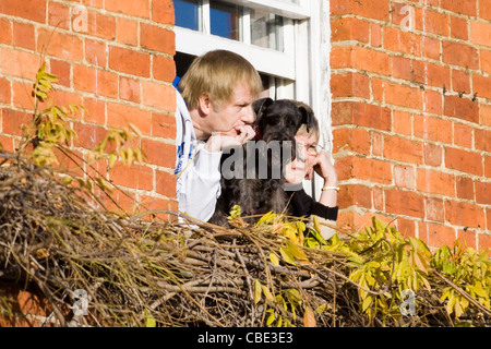 A Family and Their dog watching the Christmas parade in Buckingham from their top window Miniature Schnauzer - Stock Photo