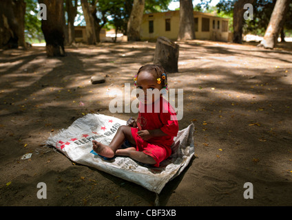 Young Girl Sitting On An Empty Sack, Village Of Dombe Grande, Angola - Stock Photo