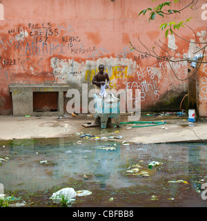 Man Doing His Laundry In The Courtyard Of The Former Grande Hotel, Now A Squat, Luanda, Angola - Stock Photo