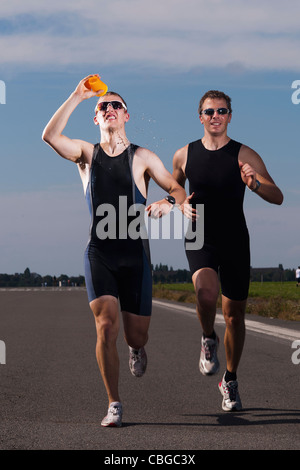 A runner pouring water on his face while running in a race - Stock Photo