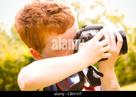 A Young boy, aged 7, using a digital SLR camera in a sunny garden. - Stock Photo
