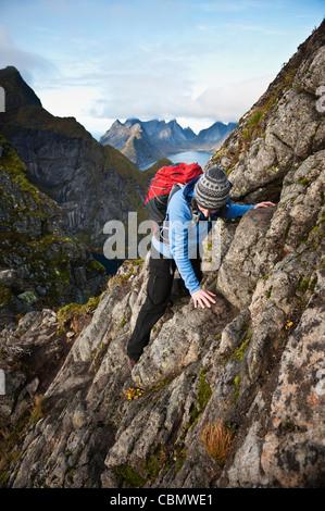 Female hiker climbs rocks near summit of Reinebringen, Moskenesoy, Lofoten Islands, Norway - Stockfoto