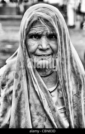 Beautiful old woman with colorful sari dress at Laxmi Narayan Temple near huge Chartarpur Road Temple in New Delhi - Stock Photo