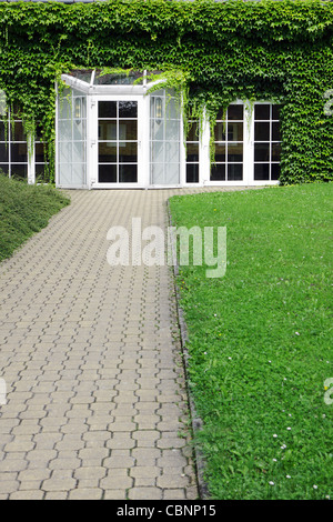 modern building with glass door and ivy - Stock Photo