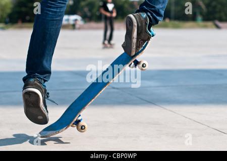 junge Skater segelnder Stunt auf seinem blauen Brett - Stockfoto
