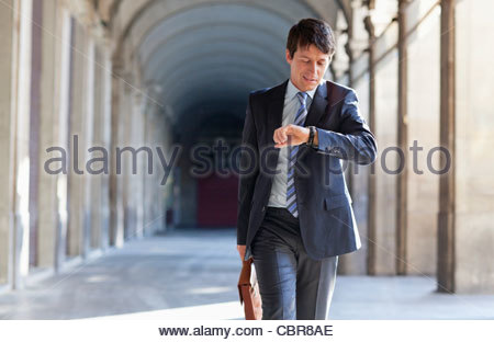 Businessman checking the time outdoors - Stock Photo