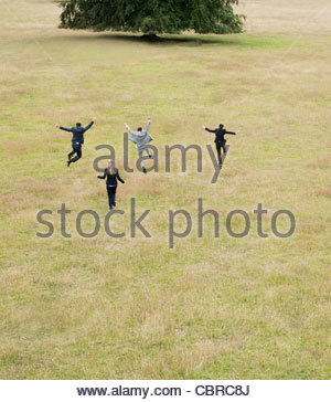 Business people running together in field - Stock Photo
