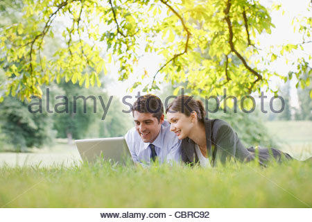 Business people laying in grass using laptop - Stockfoto