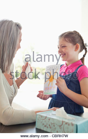 Granddaughter giving grandmother a get well soon card - Stock Photo