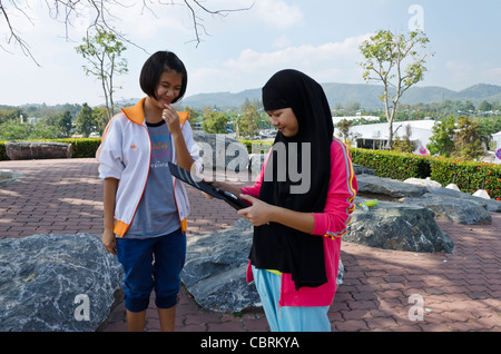 Smiling Thai Muslim teenage girl wearing long black head scarf looks at photos on her iPad with friend in northern - Stockfoto