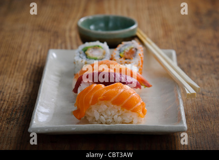Plate of Japanese sushi pieces with chopsticks and bowl with wasabi and soy - Stock Photo