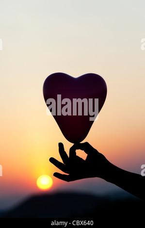 Hand holding heart shape balloon silhouette against sunset - Stockfoto