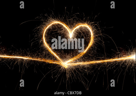 Heart shape made with sparkler at night - Stock Photo