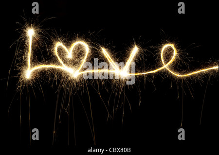LOVE written with a sparkler at night including a heart shape - Stock Photo