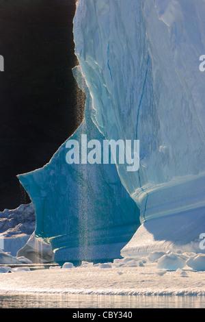 Cruising between the icebergs at Røde Ø, Scoresbysund, Greenland - Stock Photo