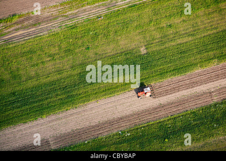 Aerial view of a tractor plowing a field - Stock Photo