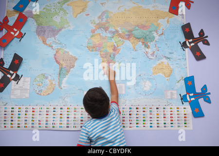 Young boy pointing to different countries on the worldwide map. - Stockfoto