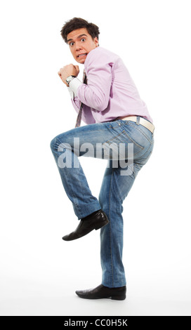 Scared man running away with grimace in his face wearing jeans, shirt and tie - Stock Photo