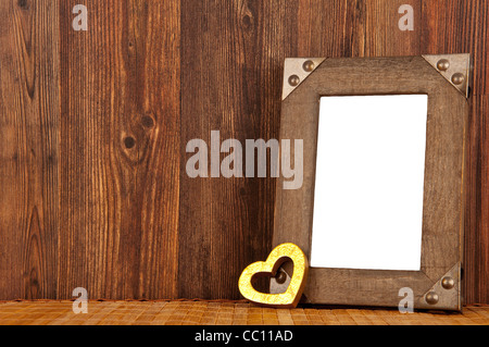 Blank wooden frame with golden heart and wooden background - Stock Photo