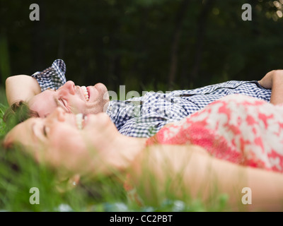 USA, New York, Putnam Valley, Roaring Brook Lake, Couple lying on grass - Stock Photo