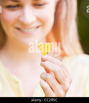 USA, New York, New York City, Manhattan, Central Park, Close up woman holding heart shaped leaf - Stock Photo