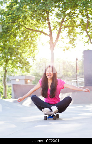 USA, Washington, Seattle, Cheerful young woman sitting on skateboard - Stock Photo