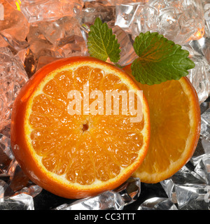 sliced oranges and green deco leaves in front of many ice cubes - Stock Photo
