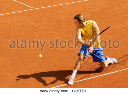 Tennis player on a red clay court in action, Nuremberg, Bavaria, Germany - Stock Photo