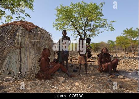 Himba villagers near the Kunene River, the border between Angola and Namibia. Kaokoland, Northern Namibia. - Stock Photo