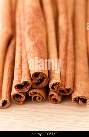 Cinnamon sticks on a wooden table top surface - Stock Photo