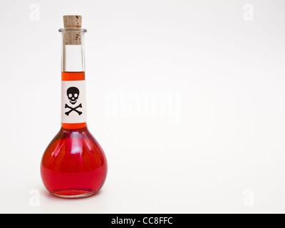 eine Flasche mit roter Flüssigkeit und einem Schild mit einem Totenkopf | a bottle with red liquid and a death's - Stock Photo