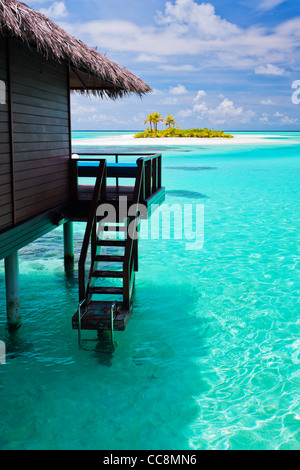 Over water bungalow with steps into amazing blue lagoon - Stock Photo