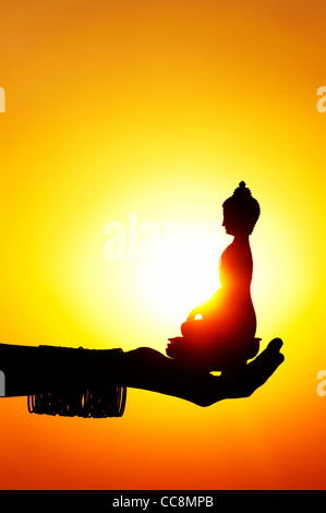 Indian girls hand holding a buddha statue against a setting sun - Stock Photo