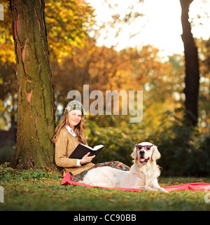 Smiling young woman relaxing in a city park with her dog - Stock Photo